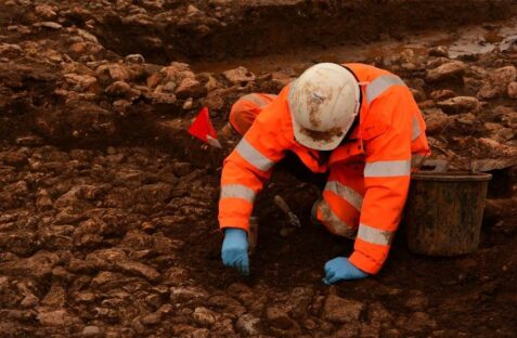 A specialist uses a trowel to dig a site